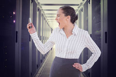 Composite image of angry businesswoman screaming at her phone. Angry businesswoman screaming at her phone against data center Royalty Free Stock Image