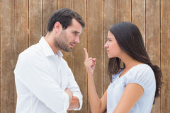 Composite image of angry couple facing off during argument Stock Images