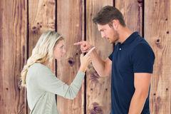 Composite image of angry couple facing off during argument. Angry couple facing off during argument against wooden planks background Stock Image