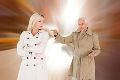Composite image of angry couple fighting in trench coats Royalty Free Stock Image