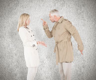 Composite image of angry couple fighting in trench coats Royalty Free Stock Photography