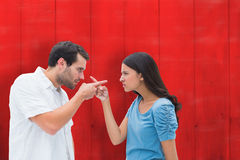 Composite image of angry couple pointing at each other Royalty Free Stock Photos