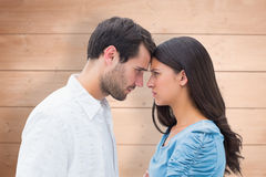Composite image of angry couple staring at each other. Angry couple staring at each other against overhead of wooden planks Royalty Free Stock Photography