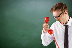 Composite image of angry geeky businessman holding telephone Royalty Free Stock Image