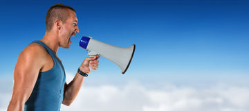 Composite image of angry male trainer yelling through megaphone Stock Photo