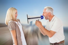 Composite image of angry man shouting at girlfriend through megaphone Stock Photography