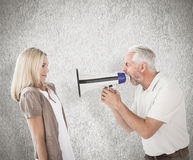 Composite image of angry man shouting at girlfriend through megaphone Stock Image