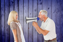 Composite image of angry man shouting at girlfriend through megaphone Stock Photo