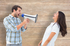 Composite image of angry man shouting at girlfriend through megaphone. Angry men shouting at girlfriend through megaphone against wooden surface with planks royalty free stock images