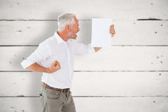 Composite image of angry man shouting at piece of paper Stock Image