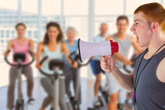 Composite image of angry personal trainer yelling through megaphone Royalty Free Stock Photo