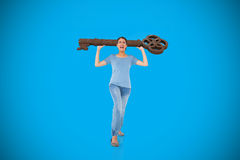 Composite image of annoyed brunette carrying large key Royalty Free Stock Images