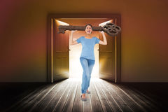 Composite image of annoyed brunette carrying large key Royalty Free Stock Image