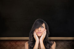 Composite image of anxious brown haired model posing holding her head Royalty Free Stock Images