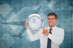 Composite image of anxious businessman holding and showing a clock Stock Image
