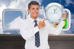 Composite image of anxious businessman holding and showing a clock Stock Photo