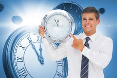 Composite image of anxious businessman holding and showing a clock Stock Images