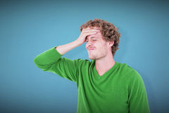 Composite image of anxious casual man standing with hand on forehead. Anxious casual man standing with hand on forehead  against blue background Stock Image