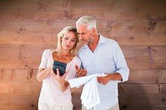 Composite image of anxious couple working out their bills Royalty Free Stock Photos