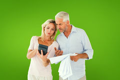 Composite image of anxious couple working out their bills Stock Photo