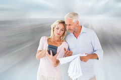 Composite image of anxious couple working out their bills Royalty Free Stock Photography