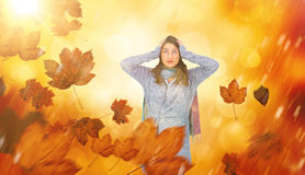 Composite image of anxious pretty brunette wearing winter clothes posing. Anxious pretty brunette wearing winter clothes posing against orange abstract light Royalty Free Stock Images