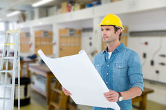 Composite image of architect holding blueprint in house Royalty Free Stock Photo