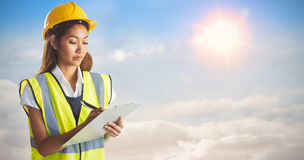 Composite image of architect woman with yellow helmet and plans Royalty Free Stock Images