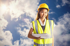 Composite image of architect woman with yellow helmet and plans Stock Images