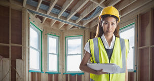 Composite image of architect woman with yellow helmet and plans Stock Photo