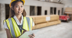 Composite image of architect woman with yellow helmet and plans Stock Image