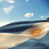 Composite image of argentina flag waving in wind. Argentina flag waving in wind against blue sky with clouds royalty free stock photos