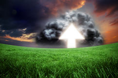 Composite image of arrow in cloud. Against green field under orange sky Royalty Free Stock Photo