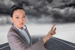 Composite image of asian businesswoman pointing Stock Images