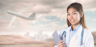 Composite image of asian doctor holding clipboard Royalty Free Stock Images