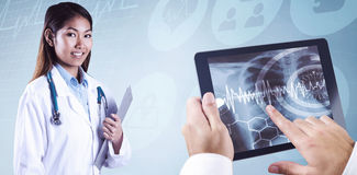 Composite image of asian doctor holding clipboard Royalty Free Stock Photography