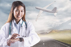 Composite image of asian doctor using her smart watch Stock Image