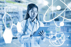 Composite image of asian doctor using tablet. Asian doctor using tablet against close up of shelves of drugs Royalty Free Stock Photography