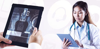 Composite image of asian doctor using tablet Stock Images
