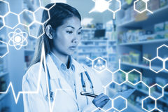 Composite image of asian doctor writing on files Royalty Free Stock Images