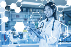 Composite image of asian doctor writing on files Stock Photos