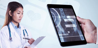 Composite image of asian doctor writing on files Royalty Free Stock Photos