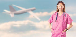 Composite image of asian nurse with stethoscope looking at the camera Stock Photography