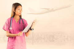 Composite image of asian nurse with stethoscope looking at the camera Stock Photo