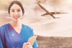 Composite image of asian nurse with stethoscope looking at the camera against a white screen Royalty Free Stock Photos