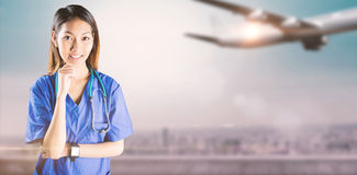 Composite image of asian nurse thinking with hand on chin royalty free stock image