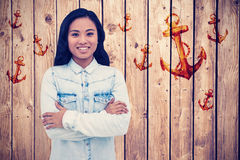Composite image of asian woman with arms crossed smiling Royalty Free Stock Photography