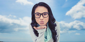 Composite image of asian woman blowing kiss to the camera Stock Image