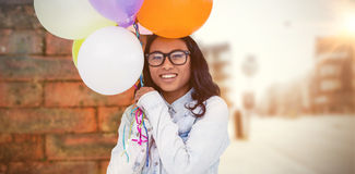 Composite image of asian woman holding colorful balloons Royalty Free Stock Photography