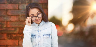 Composite image of asian woman holding eyeglasses royalty free stock images